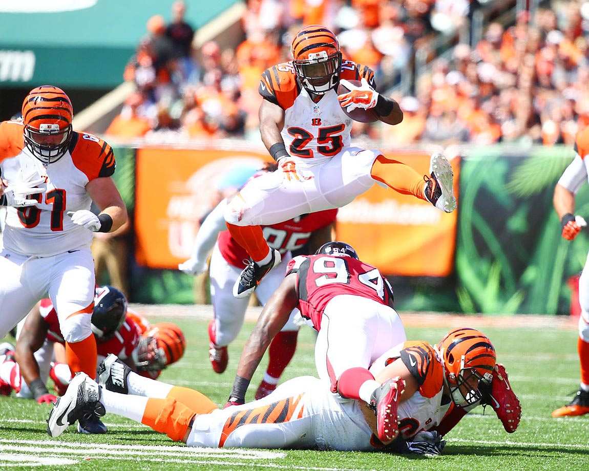 Giovani Bernard of the Cincinnati Bengals hurdles Jonathan Massaquoi of the Falcons.