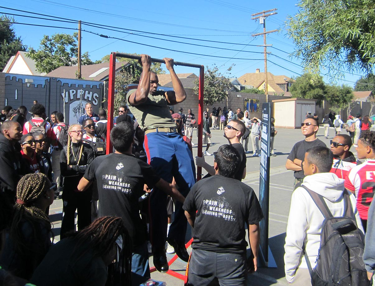A representative of the U.S. Marine Corps demonstrates proper pull-up technique for View Park High students at an event to honor Nia Toliver, the SI High School Athlete of the Month.