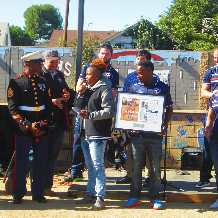 Nia Toliver, SI's High School Athlete of the Month, takes the microphone to thank her family and teammates as USA Rugby national men's sevens player Carlin Isles holds a framed copy of the issue of SI in which she appears.
