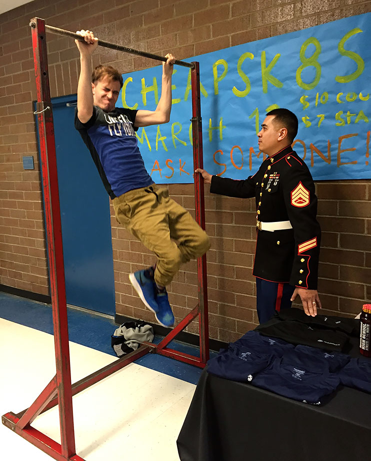 A Bingham student takes the U.S. Marine Corps' pull-up bar challenge as SSgt Virak Keo looks on.
