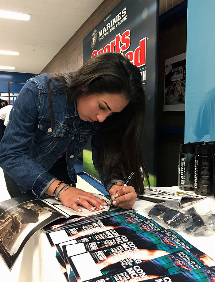 Sophia signs a copy of her issue of SI for a friend.