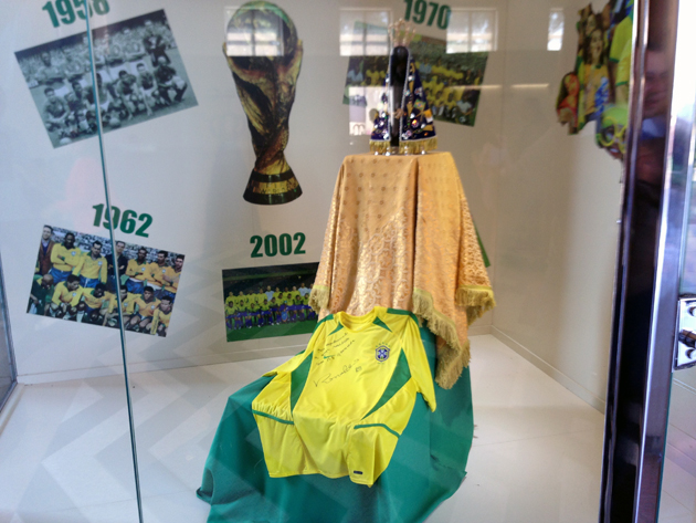 Ronaldo visited the church before and after the 2002 World Cup, which Brazil subsequently won. So Ronaldo left this signed jersey; which rests at the bottom of the shrine; a small, jeweled crown on top. The walls behind the jersey list the years of Brazil's five titles and showcase paintings of players and of fans.