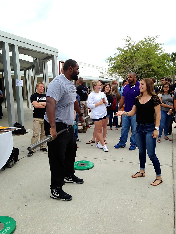 Savannah helps Timber Creek grad and NFL center Lemuel Jeanpierre with his snatch lift technique.
