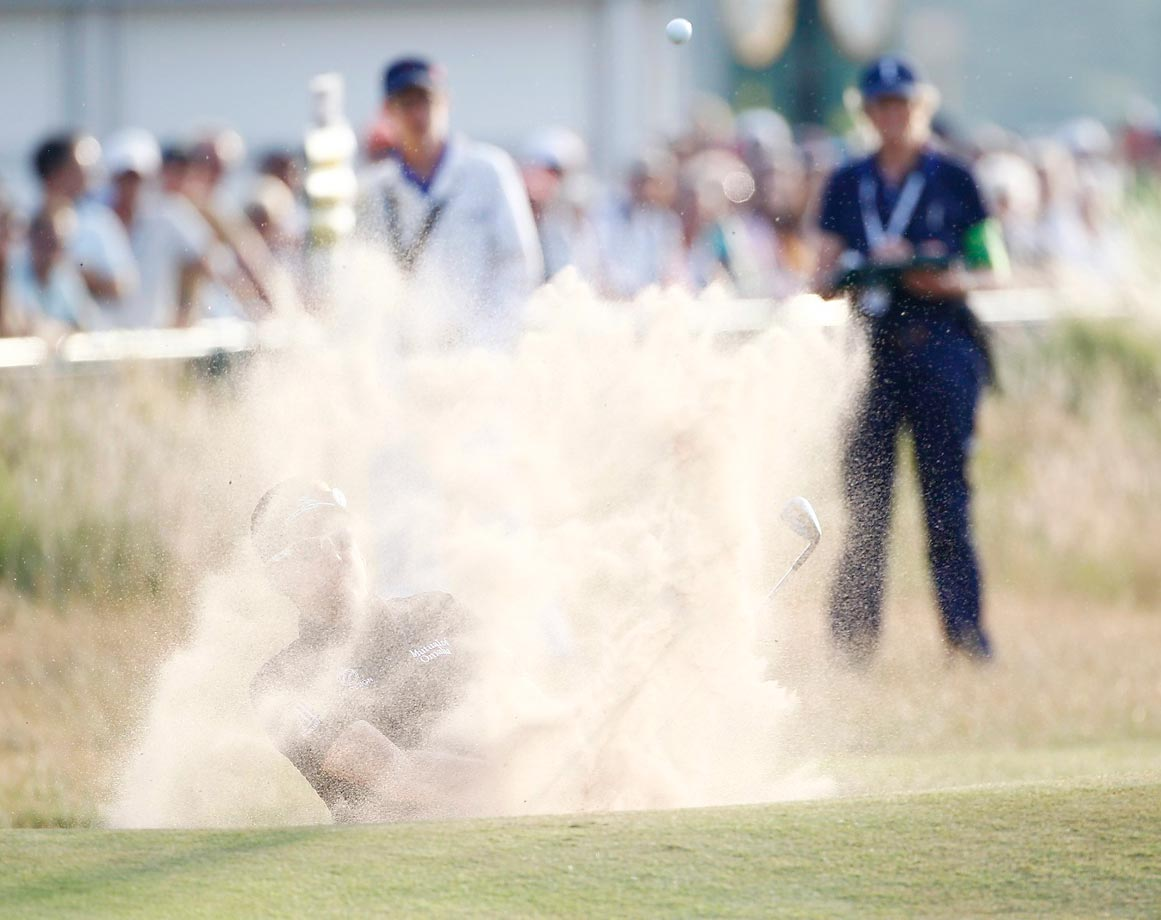 Ian Poulter of England hits out of the bunker on the 18th hole of the second round at the 2014 Open Championship in Liverpool, England.