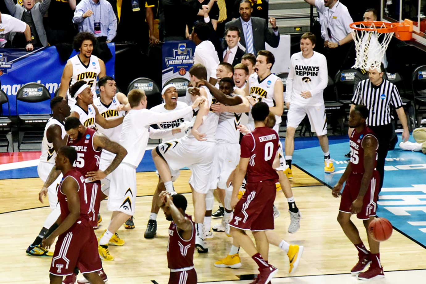 Iowa players storm the court to celebrate the last-second, game-winning basket against Temple in overtime.