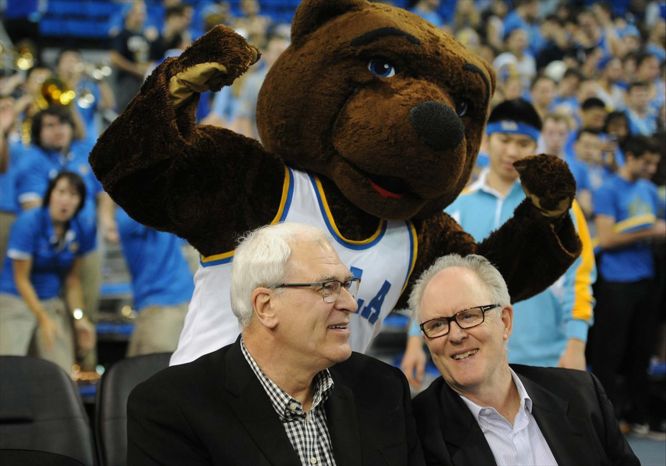Phil Jackson and John Lithgow with UCLA mascot Joe Bruin at a 2014 game between the Arizona Wildcats and the UCLA Bruins at Pauley Pavilion.
