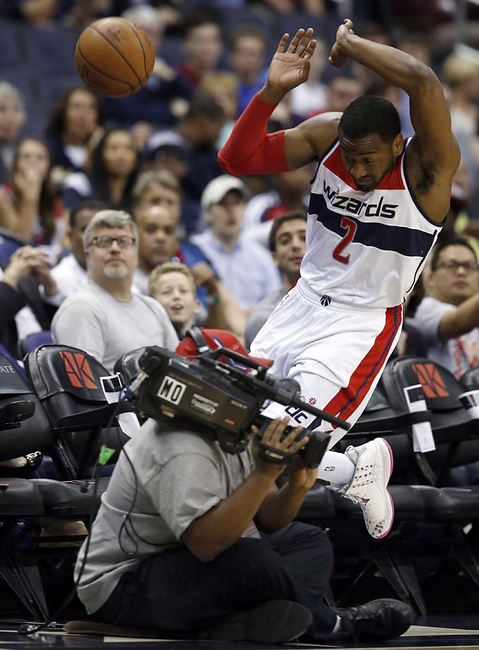 Washington Wizards guard John Wall tries to avoid a camera operator as he chases a loose ball in the first half of an NBA basketball game against the Atlanta Hawks, Sunday, April 12, 2015, in Washington.