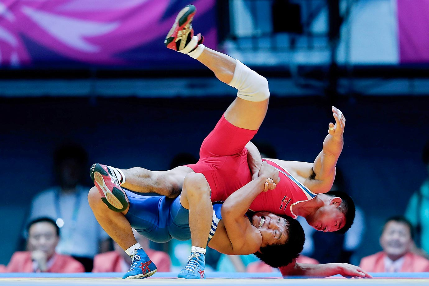 Jong Hakjin (red) of North Korea competes with Kaliyev Rassul of Kazakhstan in the wrestling men's freestyle 57 kg final of the Asian Games.