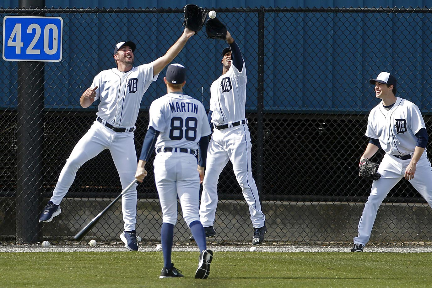 Detroit Tigers pitchers Justin Verlander, left , and Al Alburquerque, center, go after a ball hit by coach Matt Martin during a pepper game near the outfield wall, part of a baseball spring training workout.