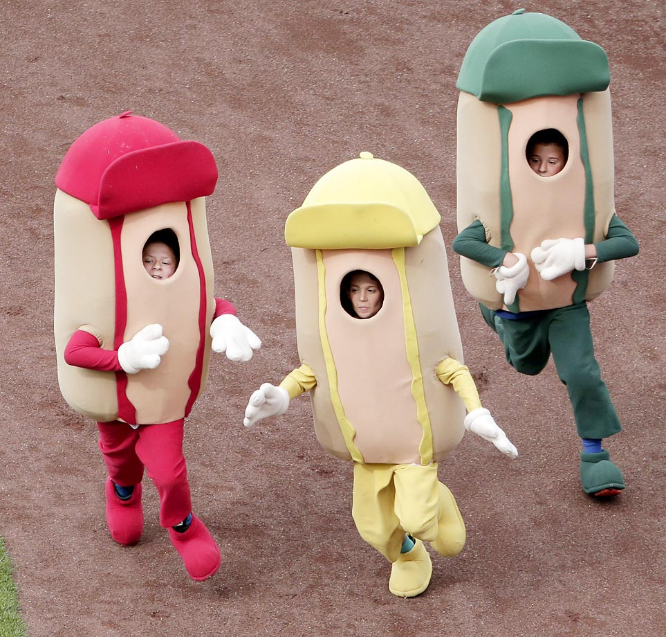 Kids dressed as hot dogs compete in a race during the fourth inning of the game between the Kansas City Royals and the Cleveland Indians.