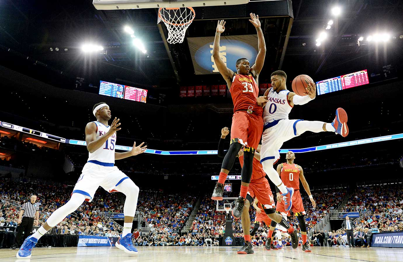 Here are some of the images that caught our eye on a night when Kansas, Oklahoma, Oregon and Villanova advanced to the Elite Eight of the NCAA Tournament. Pictured here, Frank Mason III of Kansas passes around Diamond Stone of Maryland.