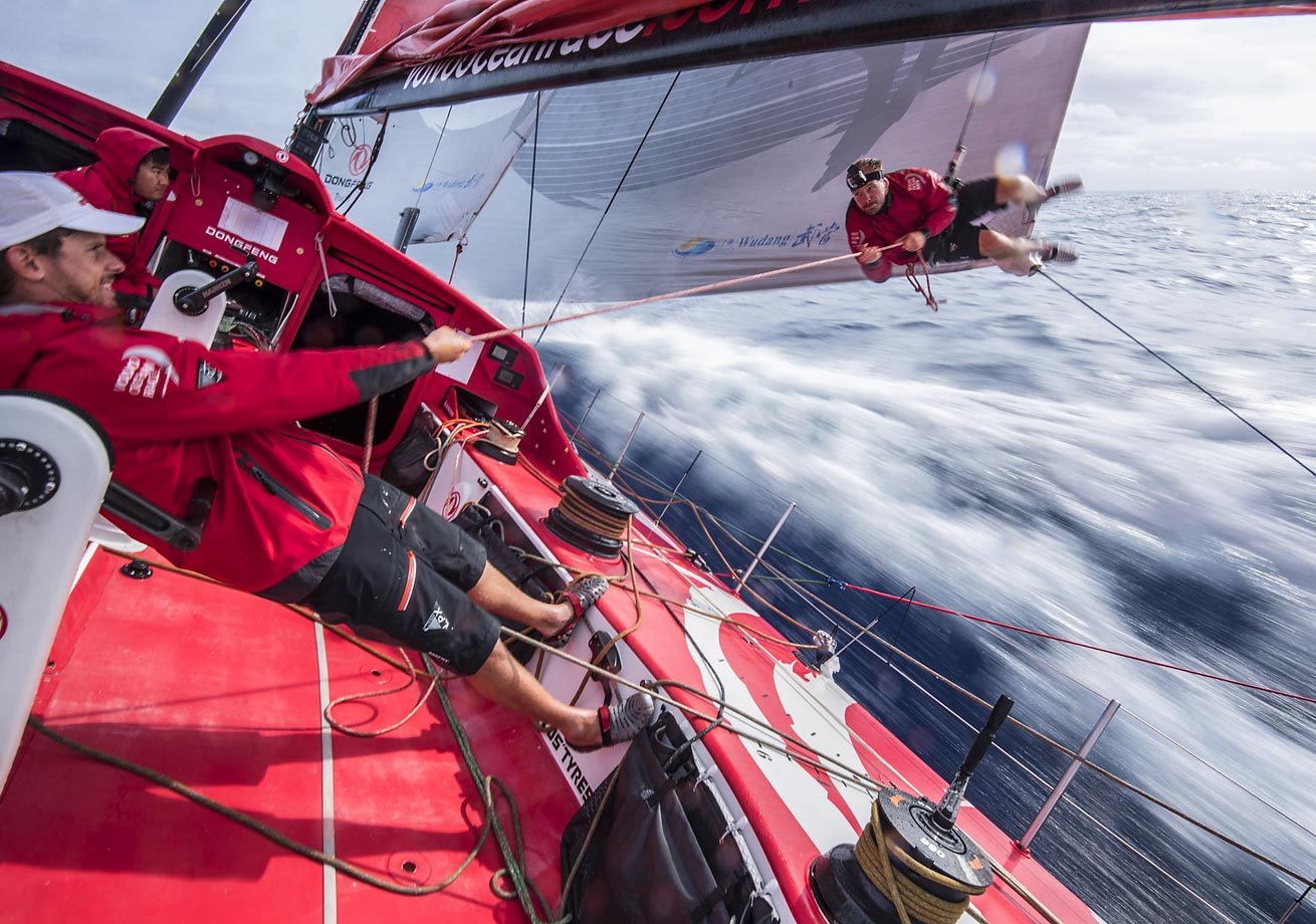 Kevin Escoffier is finished checking the leech line so Thomas Rouxel pulls him in during the Volvo Ocean Race.