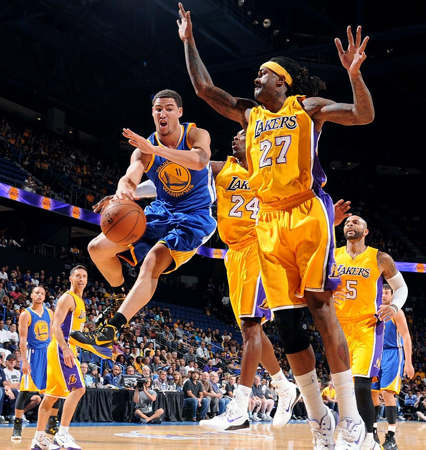 Klay Thompson of the Golden State Warriors passes against Jordan Hill and Kobe Bryant of the Lakers. The Warriors won the preseason game 108-71.