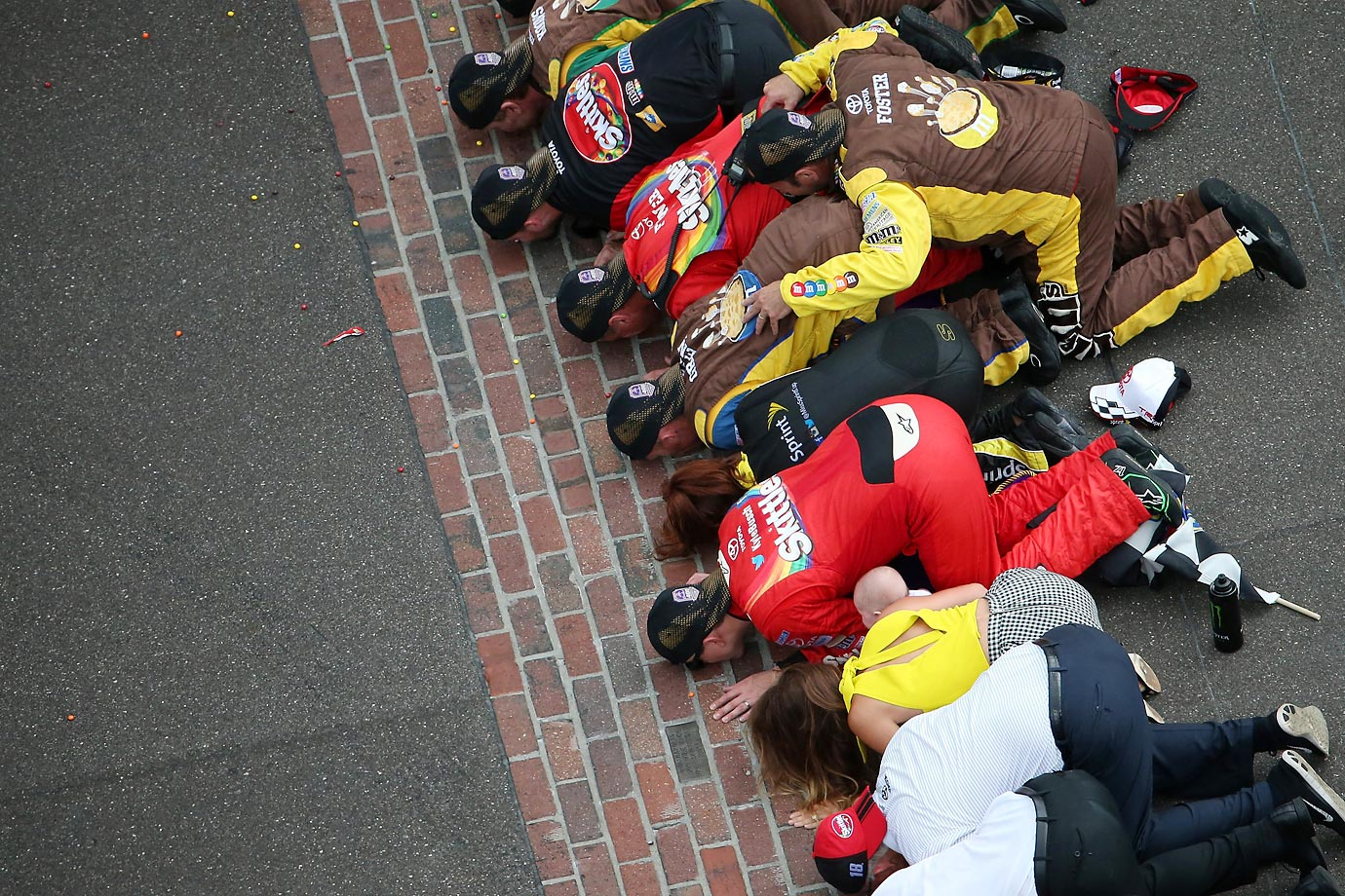 Kyle Busch celebrates with his team by kissing the bricks after winning the NASCAR Sprint Cup Series race at the Brickyard.