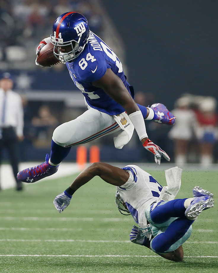 New York Giants tight end Larry Donnell leaps over Dallas Cowboys cornerback Brandon Carr.