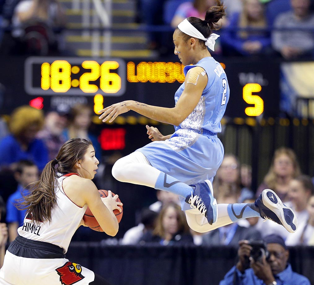 North Carolina's Latifah Coleman leaps high to stop the drive of Louisville's Jude Schimmel.