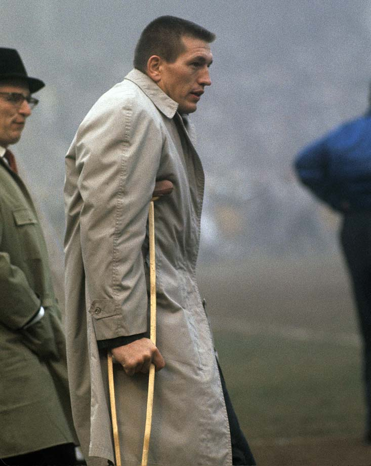 Baltimore Colts QB Johnny Unitas watches his teammates play the Green Bay Packers at Memorial Stadium. Unitas sustained a knee injury during the previous week's game.