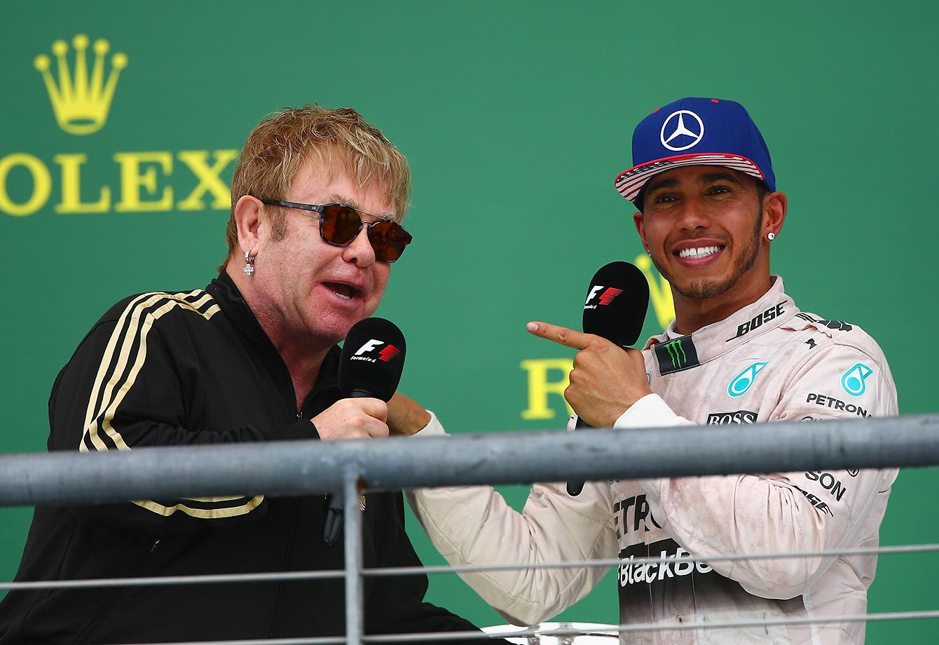 Lewis Hamilton celebrates on the podium with Elton John after winning the U.S. Formula One Grand Prix.