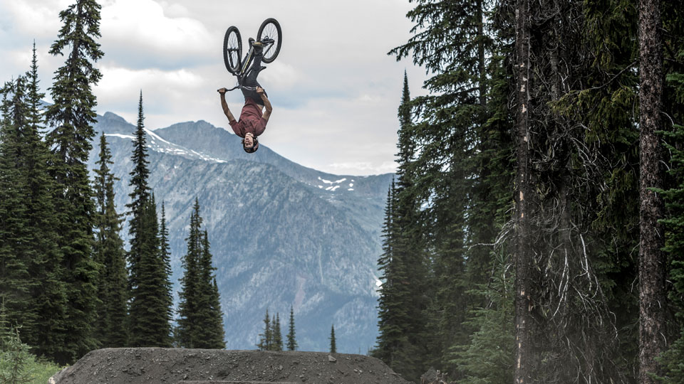 Thomas Genon, who is quickly climbing the rankings in MTB slopestyle, performs a front flip on his mountain bike at Retallack Lodge, near Nelson, BC Canada.
