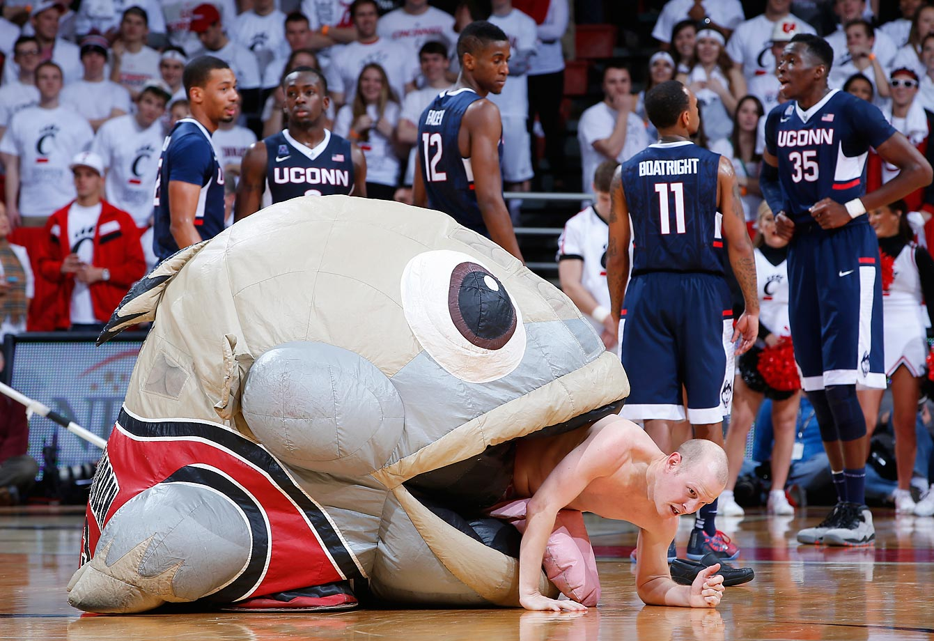 A fish named Mackerel Jordan and a fan take part in a skit during a timeout at the game between the Cincinnati Bearcats and Connecticut Huskies.