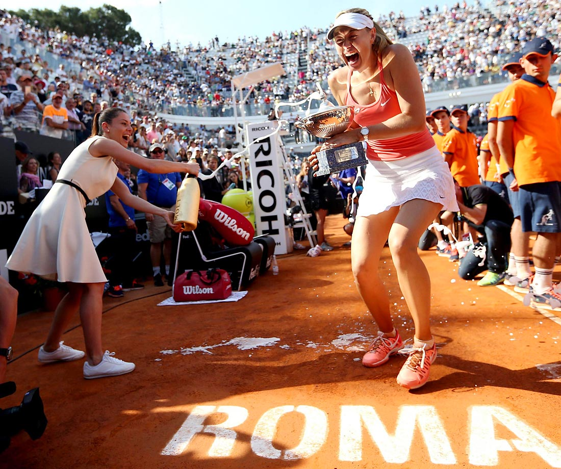 Maria Sharapova is sprayed with champagne as she holds the trophy at the end of the final match of the Italian Open tennis tournament in Rome.
