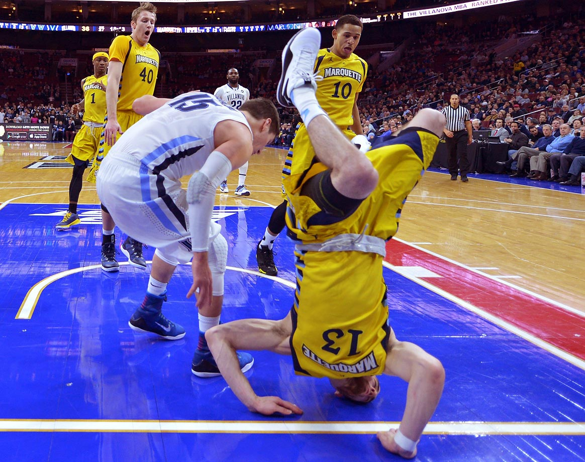 Matt Carlino of the Marquette Golden Eagles falls to the floor after being upended by Ryan Arcidiacono of the Villanova Wildcats at the Wells Fargo Center in Philadelphia. Villanova won 70-52.