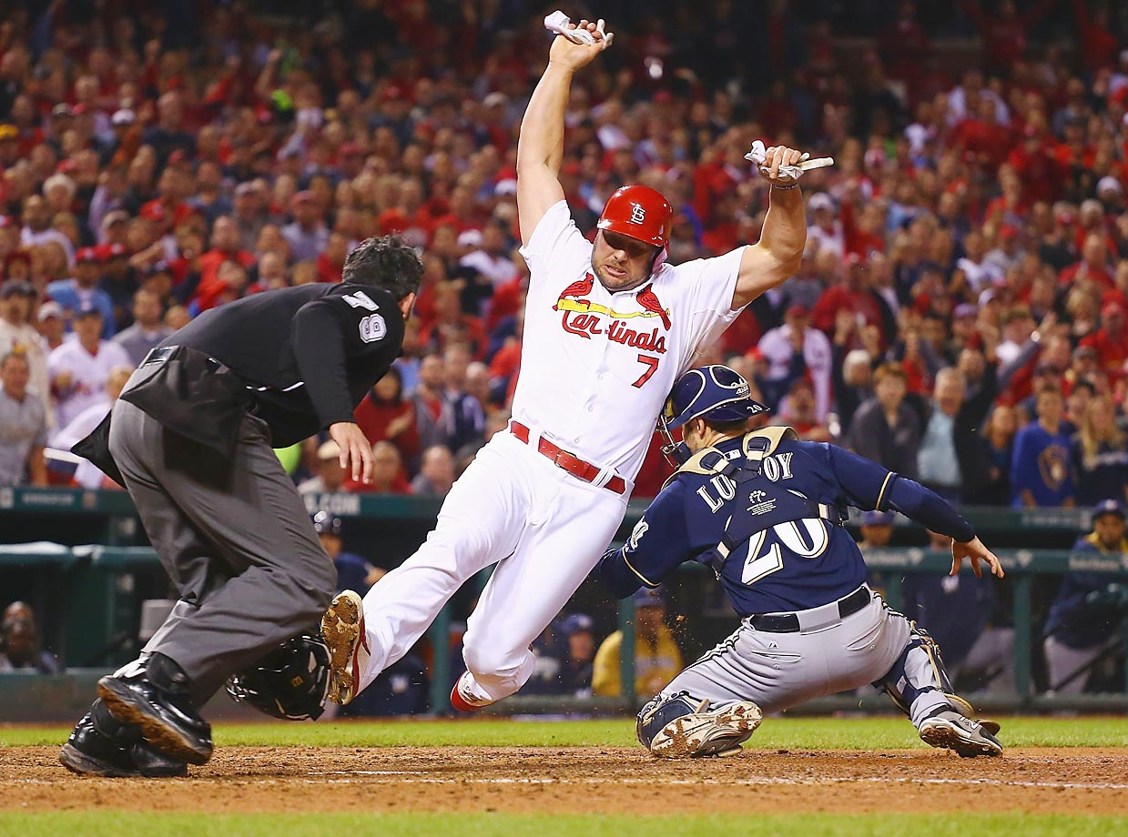 Matt Holliday scores the game-winning run for the Cardinals against Jonathan Lucroy of the Brewers.