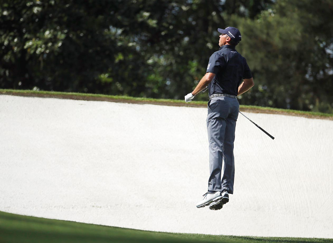 Matt Kuchar leaps up to see the pin on the fifth hole at the Masters.