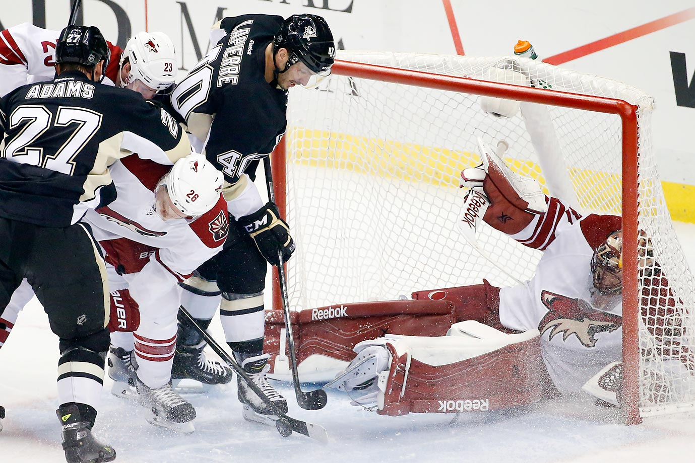 Maxim Lapierre of the Penguins' tries to reach a rebound as Mike Smith of the Coyotes falls into his net.