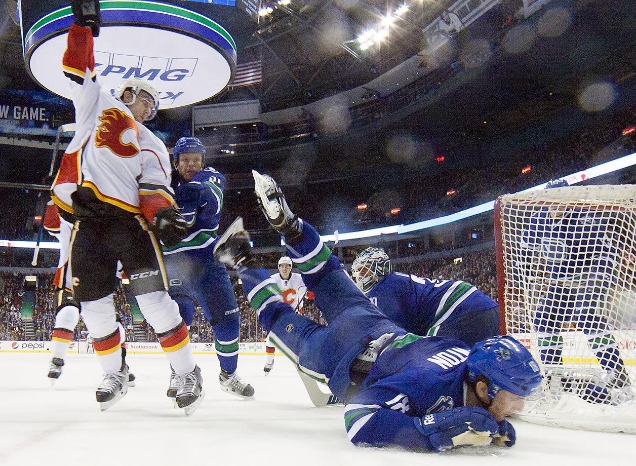 Mikael Backlund of the Calgary Flames celebrates his goal as he is checked by Derek Dorsett of the Vancouver Canucks.