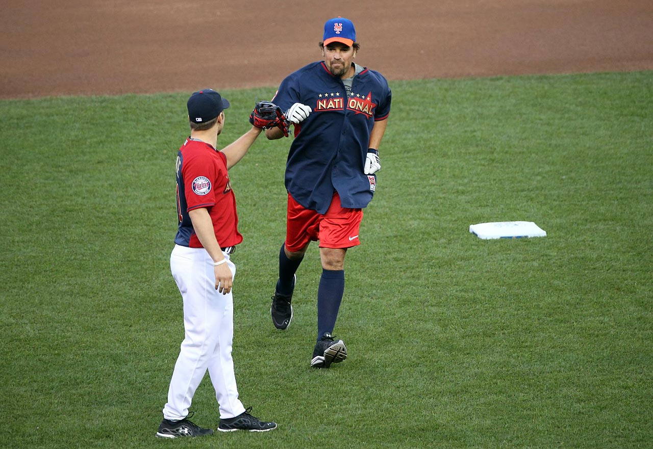 Mike Piazza gets a fist-bump from Zach Parise as he rounds the bases after hitting a home run in the 2015 All-Star Legends and Celebrity Softball Game at Target Field in Minneapolis, Minn.
