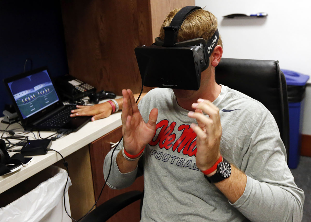 Mississippi quarterback Ryan Buchanan uses a virtual reality headset to make football play decisions on July 27, 2015 at the Manning Center in Oxford, Miss. Ole Miss is one of a growing number of football programs in the NCAA and NFL dabbling in virtual reality technology to help supplement work on the field.