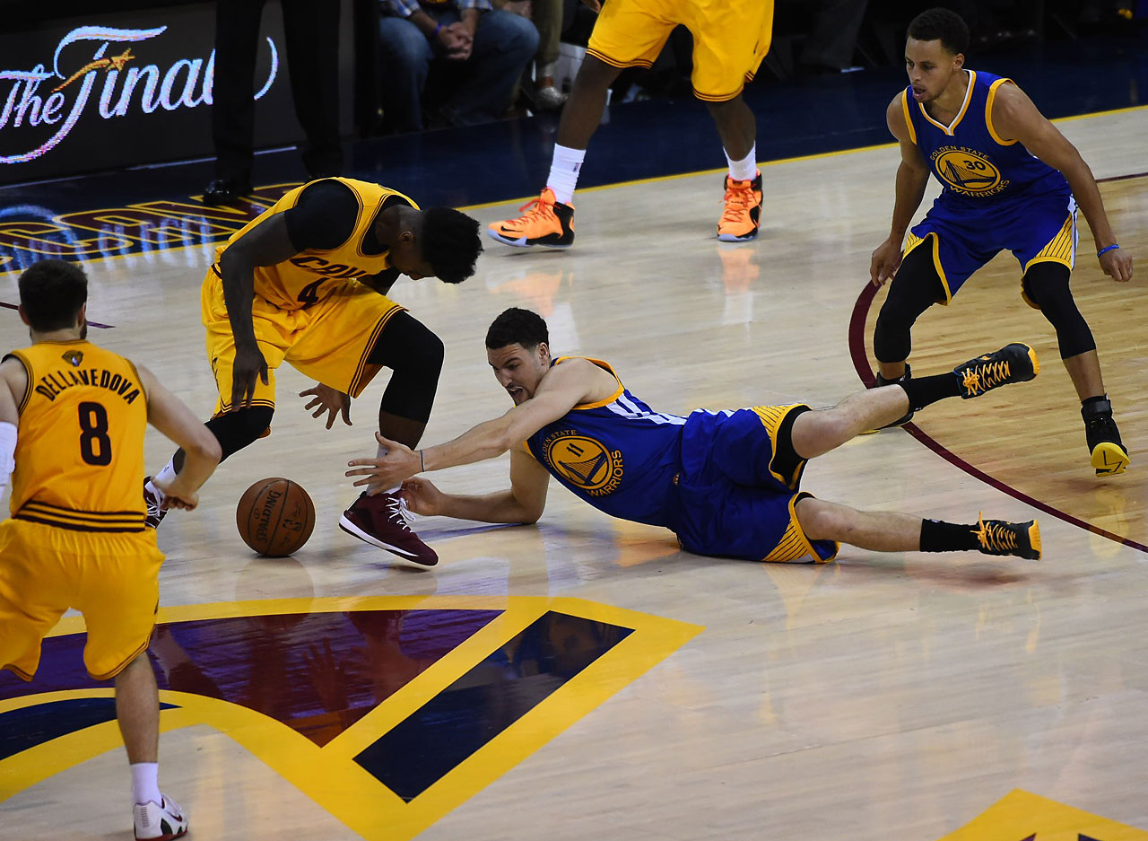 The Warriors' Klay Thompson attempts to grab a loose ball.