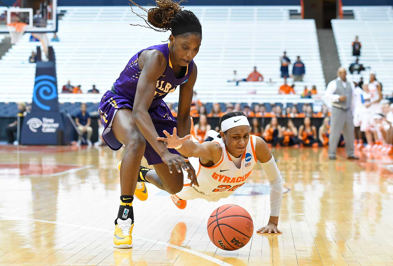 Brittney Sykes of Syracuse and Bose Aiyalogbe of Albany compete for a loose ball in the NCAA Tournament.