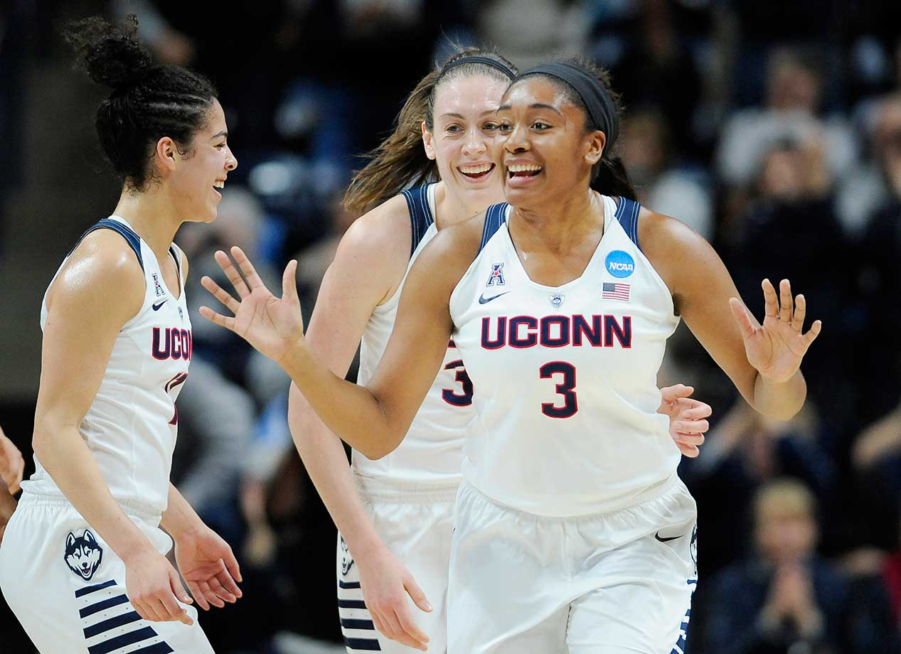 Connecticut's Morgan Tuck, right, celebrates with Kia Nurse, left, and Breanna Stewart after sinking a basket against Duquesne.