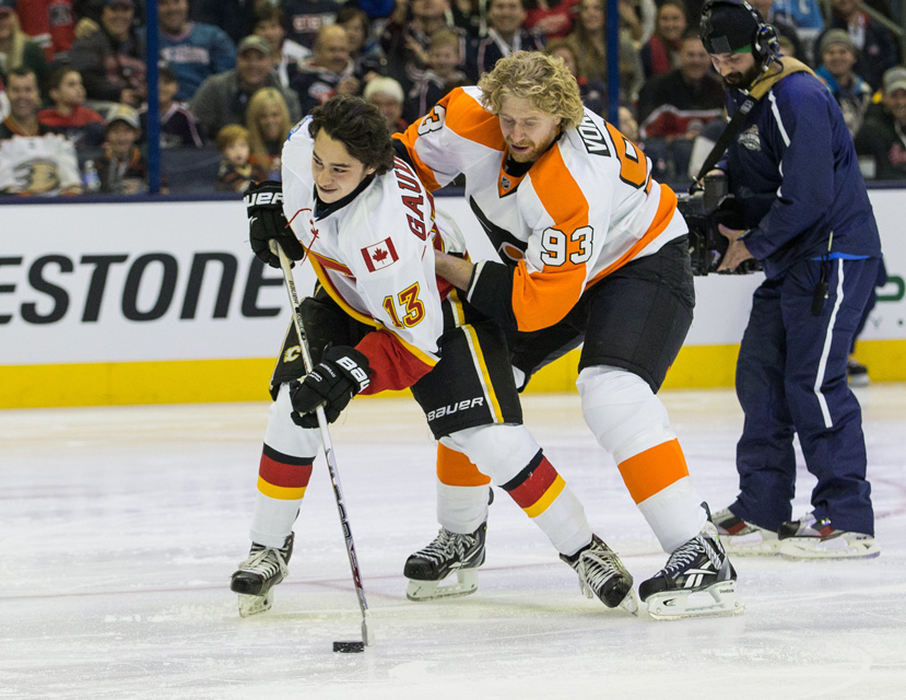 Jakub Voracek of the Philadelphia Flyers gets an assist from Flames' rookie Johnny Gaudreau during the Honda NHL Breakaway Challenge at the All-Star Skills Competition.
