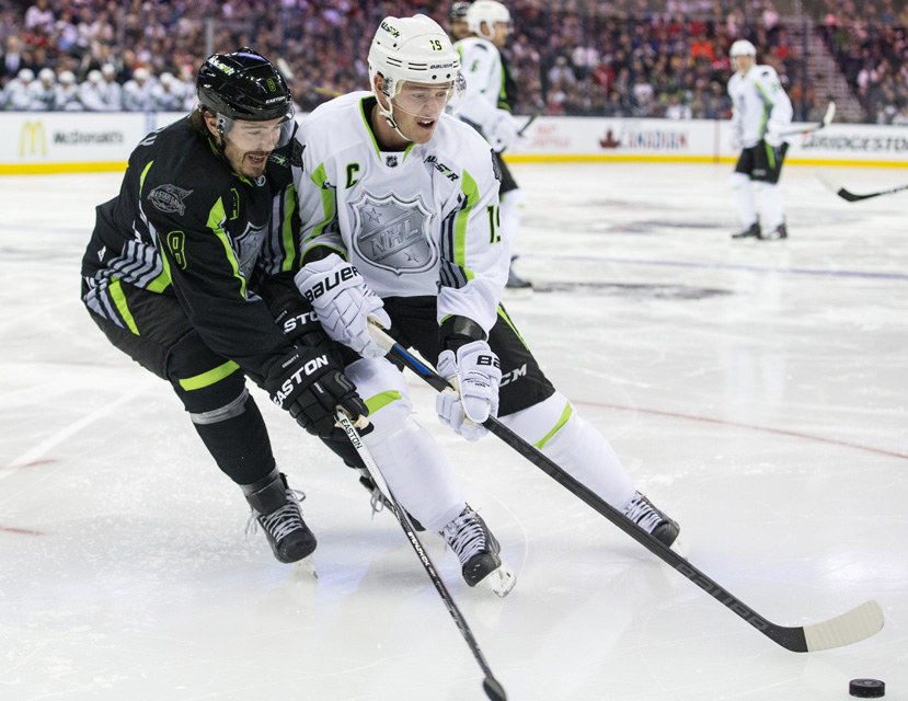 Jonathan Toews #19 of team Toews battles for a loose puck against Drew Doughty #8 of team Foligno during the 2015 NHL All-Star Game.
