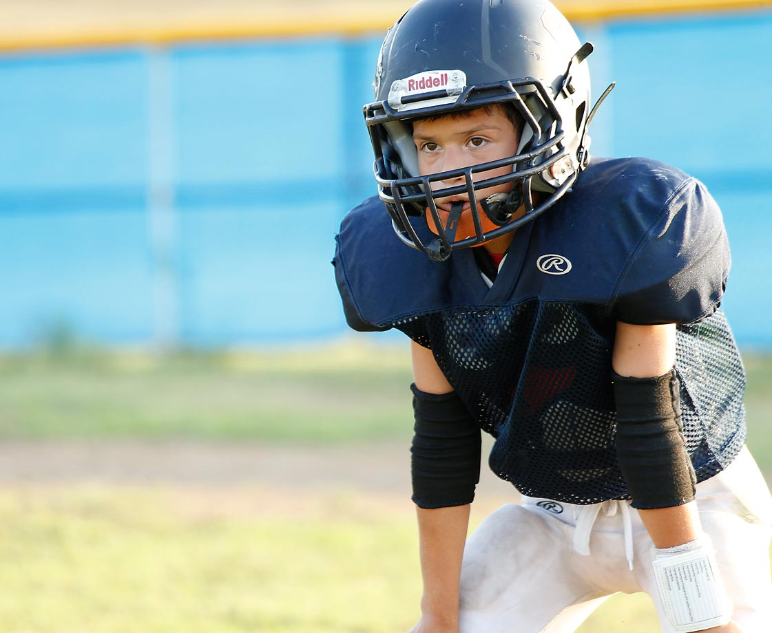 A Jr. Broncos player stands in concentration as the play is about to start.