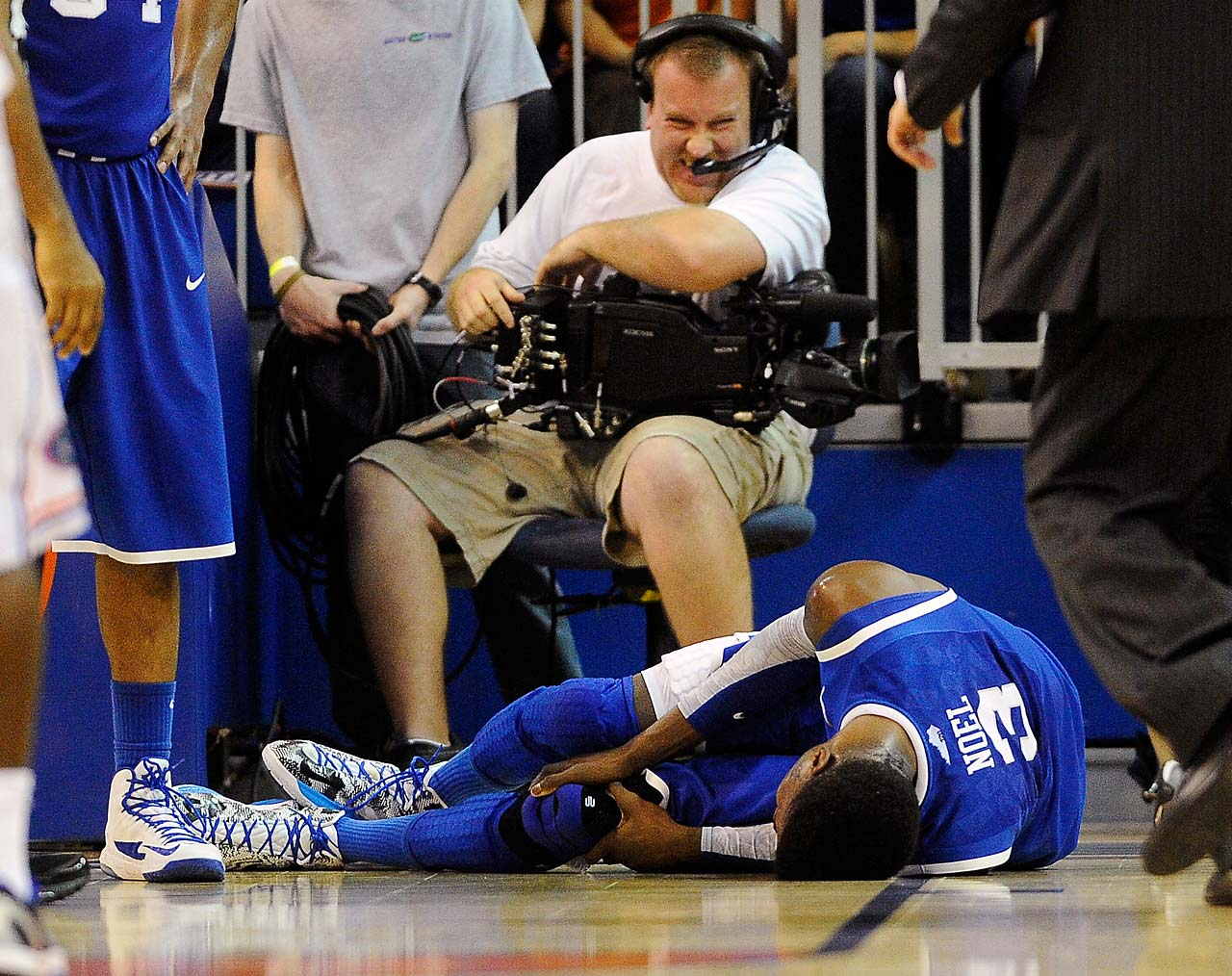A cameraman grimmaces after a collision with Kentucky forward Nerlens Noel during the second half of an NCAA college basketball game against Florida in Gainesville, Fla., in February 2013.