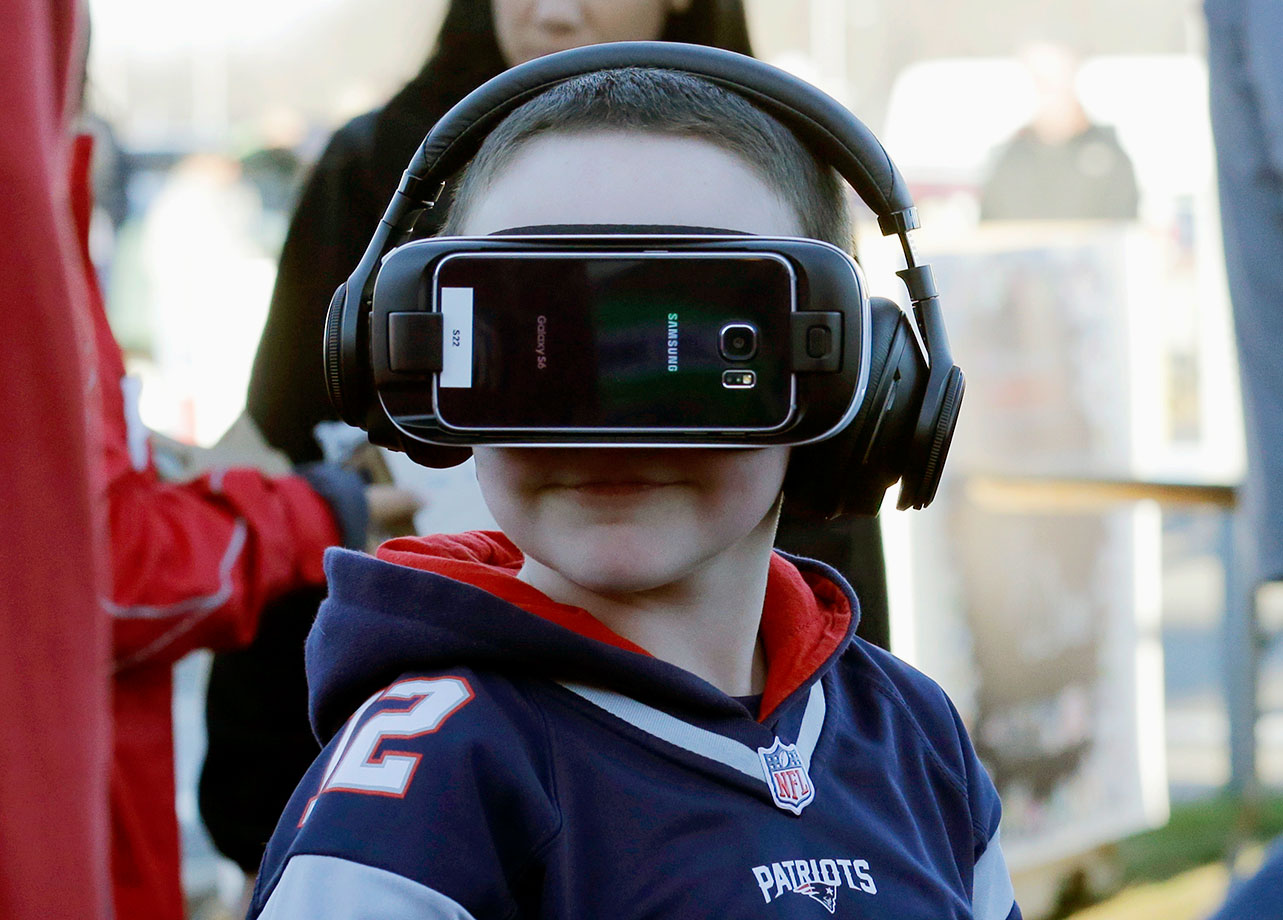 A young New England Patriots fan wears a virtual reality headset while tailgating in the parking lot of Gillette Stadium before a game against the Philadelphia Eagles on Dec. 6, 2015 in Foxborough, Mass.