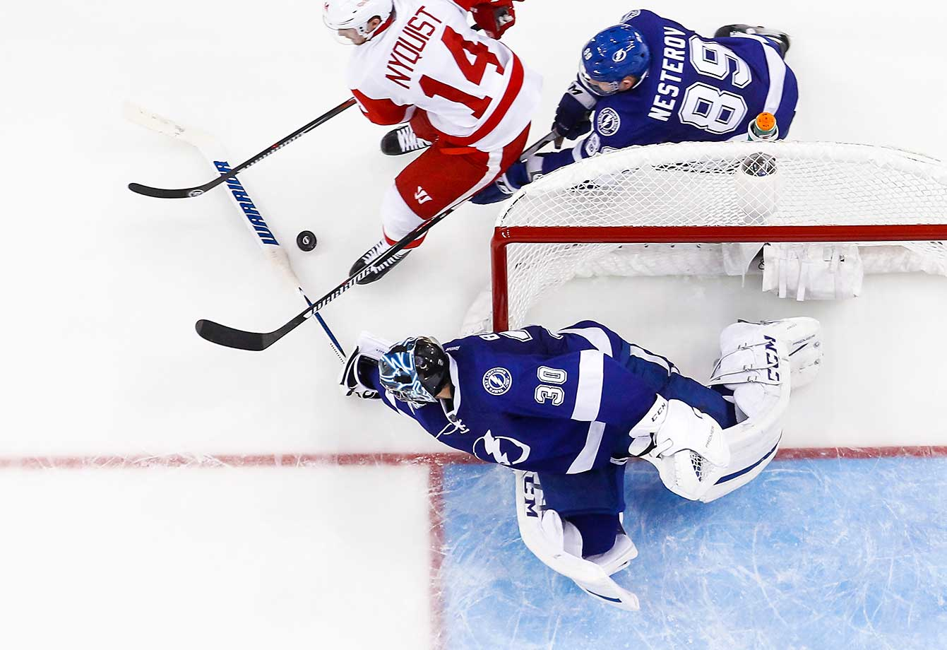 Goalie Ben Bishop of the Tampa Bay Lightning knocks the puck away from Gustav Nyquist of the Detroit Red Wings as Nikita Nesterov chases at the Amalie Arena in Tampa, Fla.