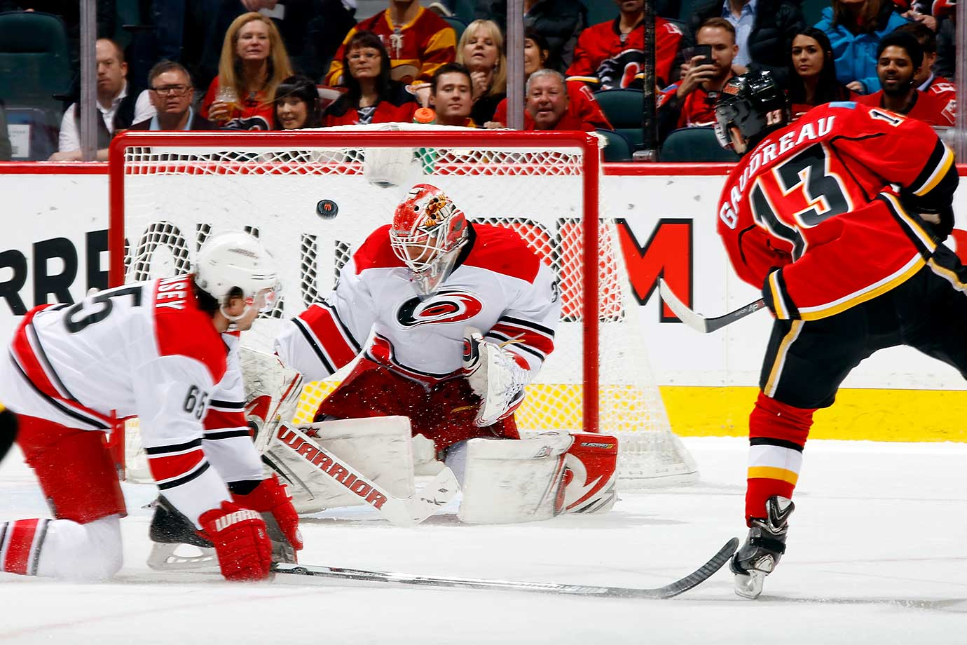 Johnny Gaudreau of the Calgary Flames shoots the puck off the crossbar against Eddie Lack of the Carolina Hurricanes at Scotiabank Saddledome in Calgary, Alberta, Canada.