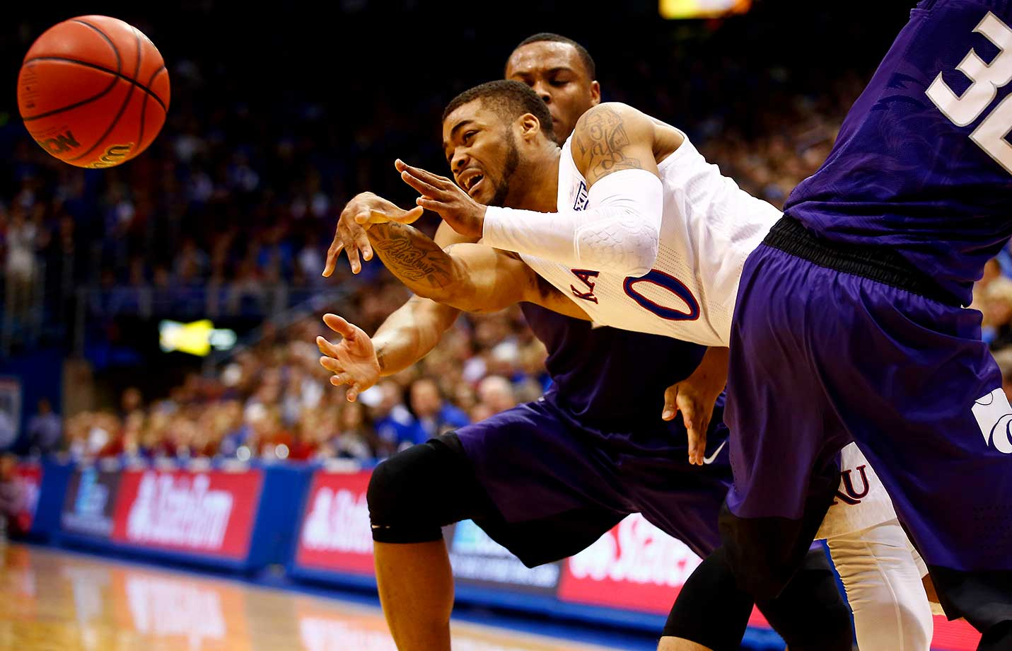 Frank Mason III of the Kansas Jayhawks passes around Dean Wade of the Kansas State Wildcats during their game at Allen Fieldhouse.