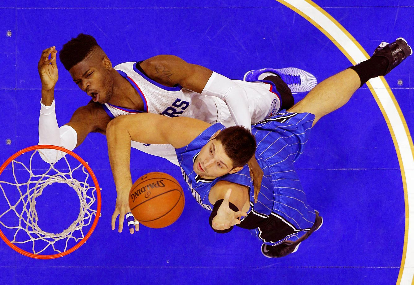 Nikola Vucevic of the Orlando Magic goes up for a shot past Nerlens Noel of the Philadelphia 76ers. The Magic won their first game of the season 91-89.