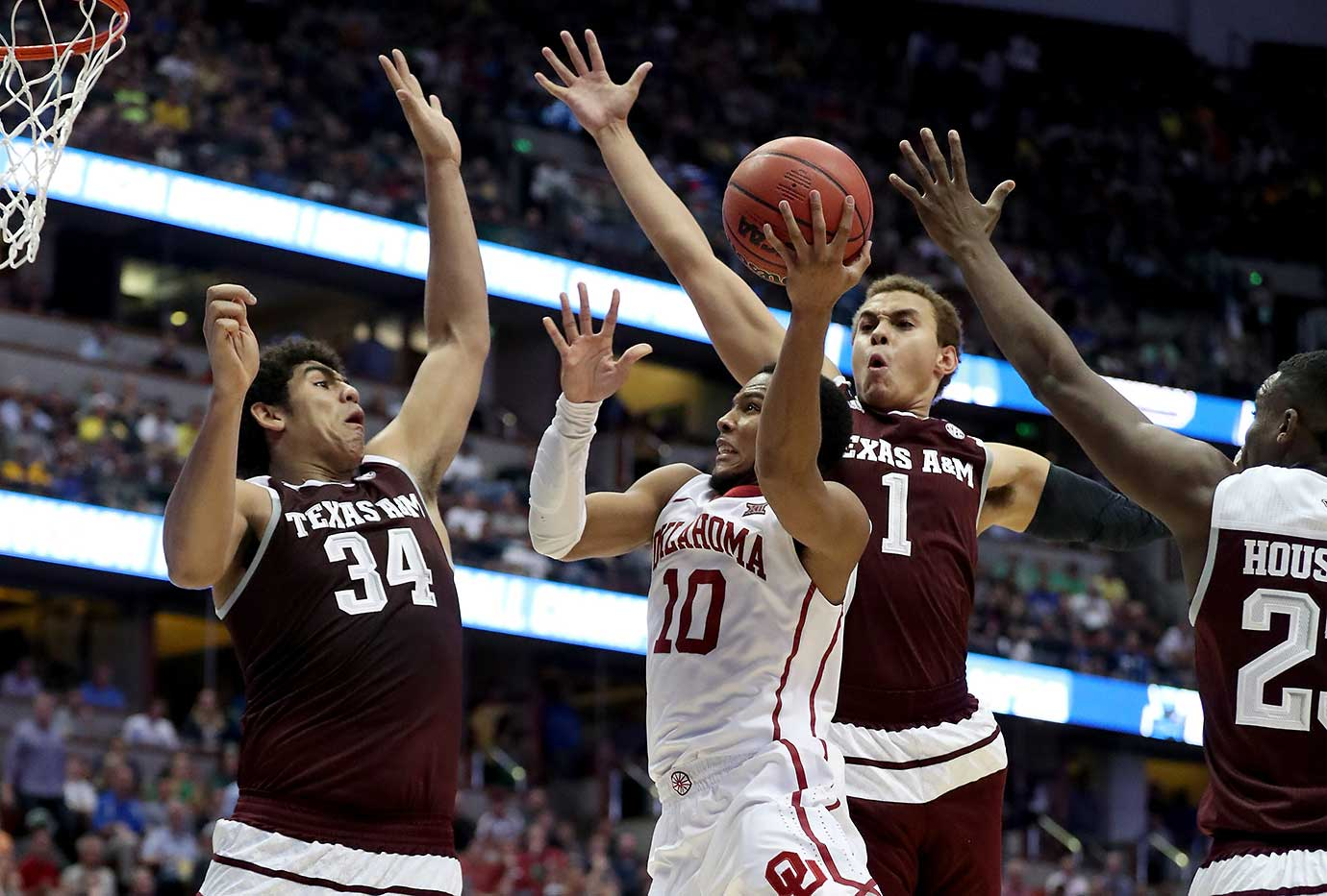 Jordan Woodard of Oklahoma goes up for a shot against Tyler Davis (34) and DJ Hogg of Texas A&M.