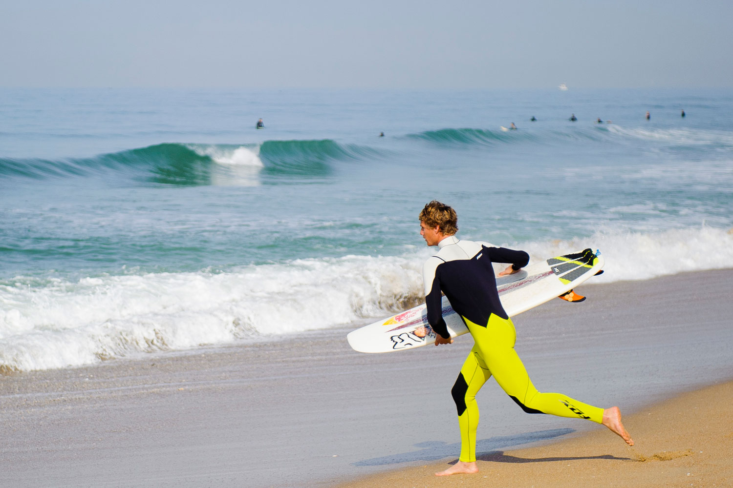 Ian Walsh running out to surf the second half of the day in the ocean.