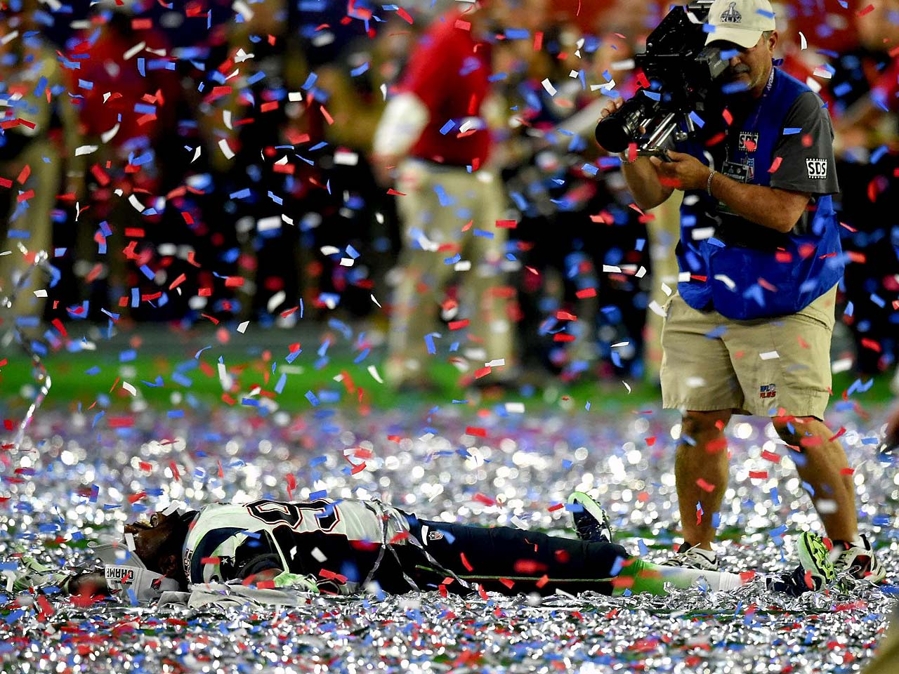 An unidentified Patriot does a confetti angel.