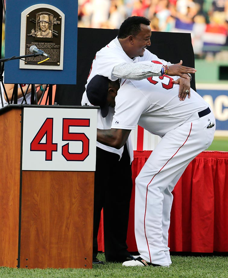 Boston Red Sox Hall of Fame pitcher Pedro Martinez embraces former teammate David Ortiz before a game at Fenway.