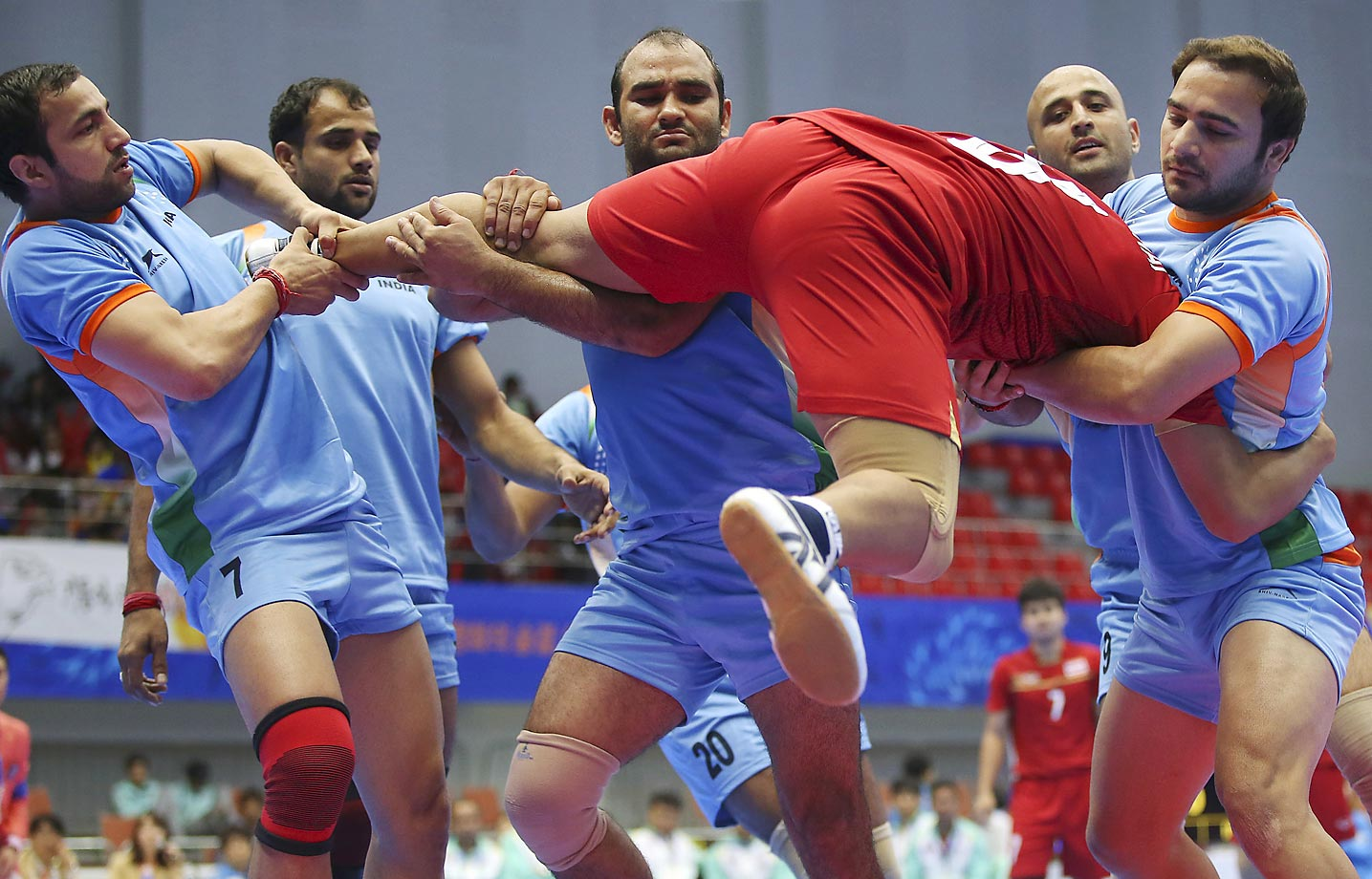 Thailand's Phuwanai Wannasaen, in red jersey, is caught by India team during the men's team kabbadi preliminary match at the 17th Asian Games in Incheon, Korea.