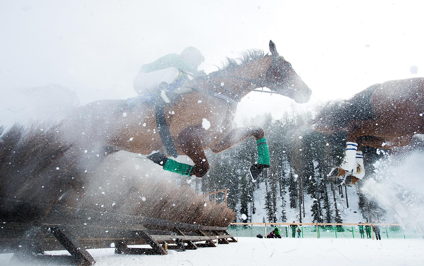 Horse jump over a barrier during the Hurdles Prix Arosa Race of the White Turf St. Moritz, in Switzerland.
